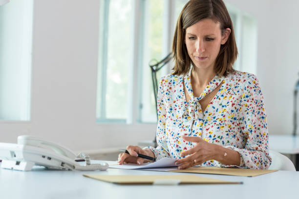 Young businesswoman sitting at her  office desk working Young businesswoman sitting at her  office desk working going through some paperwork. bureaucracy stock pictures, royalty-free photos & images