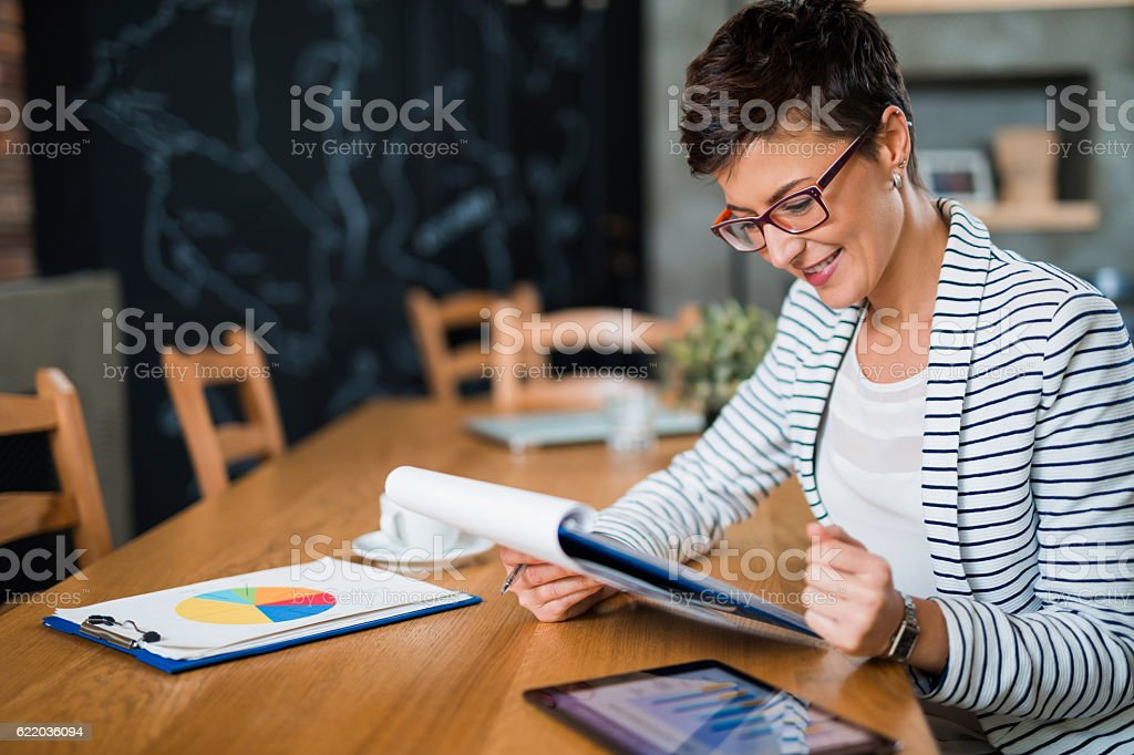 Young businesswoman sitting at the office reading business report. stock photo