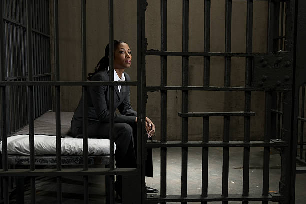 Young businesswoman sitting on bed in prison cell, looking away stock photo