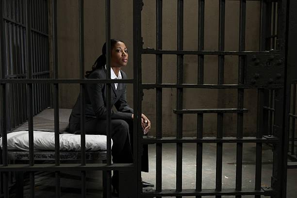 Junge Geschäftsfrau sitzt auf dem Bett in Gefängniszelle, Wegsehen – Foto
