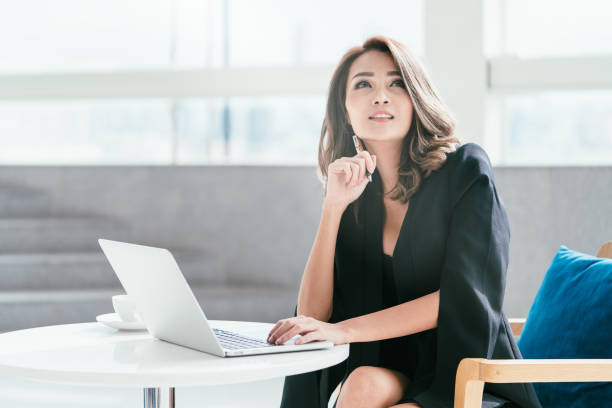 Young businesswoman sitting on the chair with her labtop. stock photo