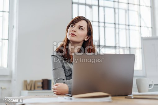 Young businesswoman sitting at her laptop in an office puzzling a problem staring up into the air with a thoughtful expression