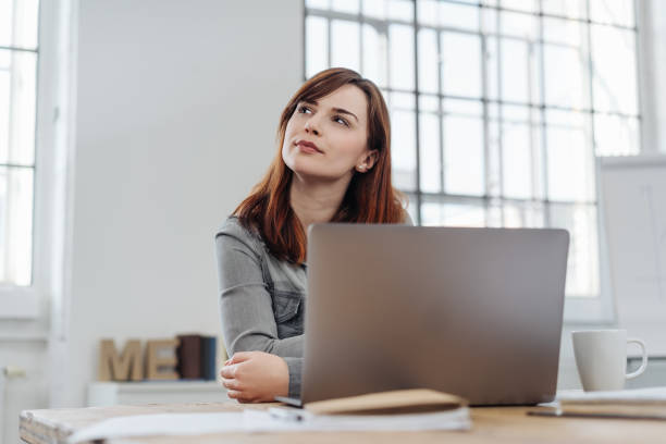 Young businesswoman sitting puzzling a problem stock photo