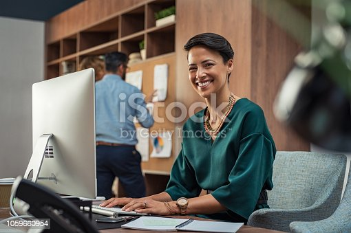 Portrait of beautiful businesswoman working on laptop and smiling. Creative glamour secretary at work in the office using computer and loooking at camera. Successful young woman sitting at office desk.