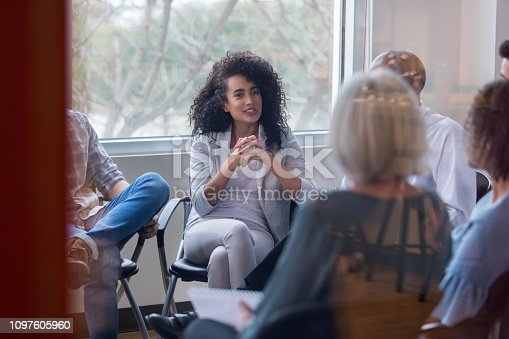 istock Young businesswoman speaks to coworkers during meeting 1097605960