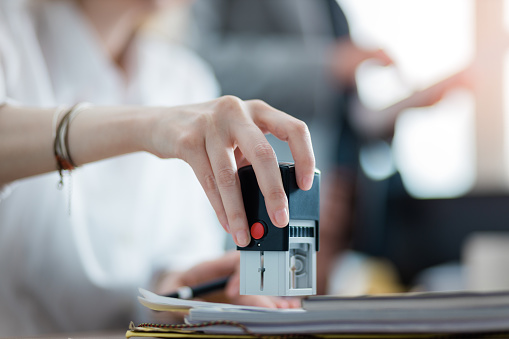 944422446 istock photo Young businesswoman stamping a document in the office 1217782415