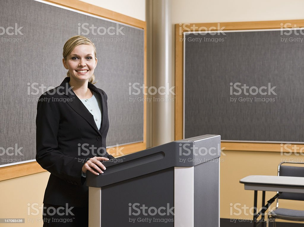Young Businesswoman Standing at Podium and Smiling royalty-free stock photo