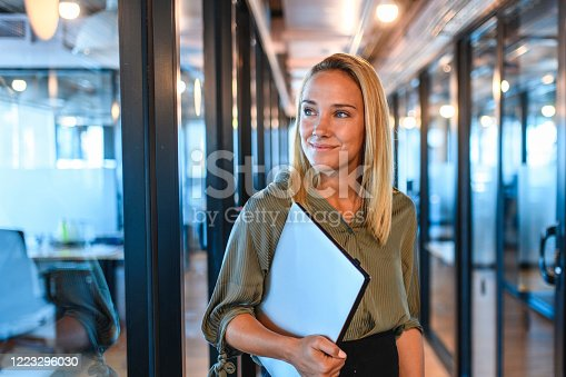 istock Young Businesswoman Standing in Office Hallway with Laptop 1223296030
