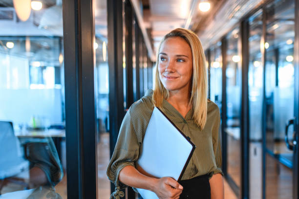 Young Businesswoman Standing in Office Hallway with Laptop stock photo