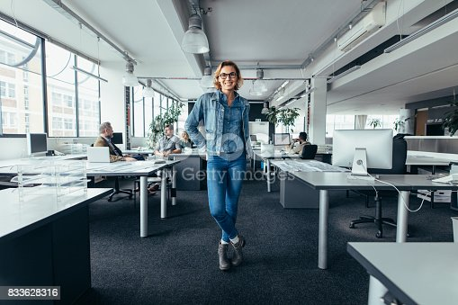 istock Young businesswoman standing in office with colleagues 833628316