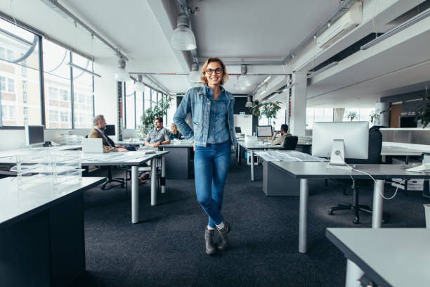 Young businesswoman standing in office with colleagues Young businesswoman standing in office with colleagues discussing in background. Happy female executive standing in workplace. full length stock pictures, royalty-free photos & images