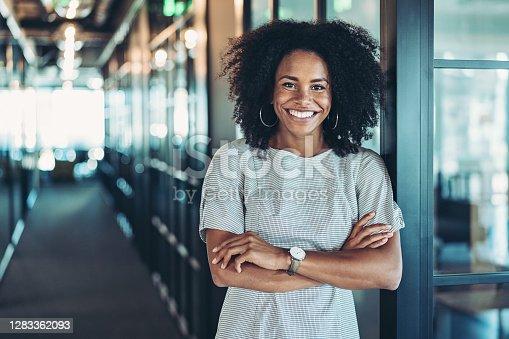 istock Young businesswoman standing in the corridor 1283362093