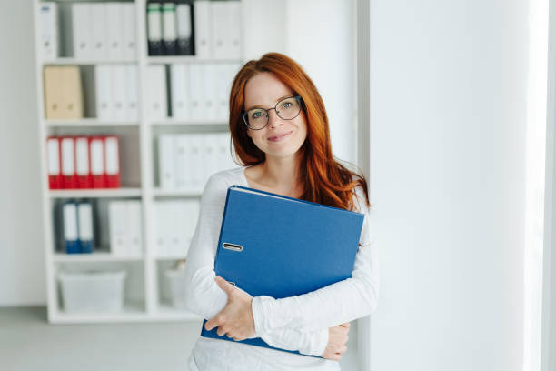 Young businesswoman standing looking at camera stock photo