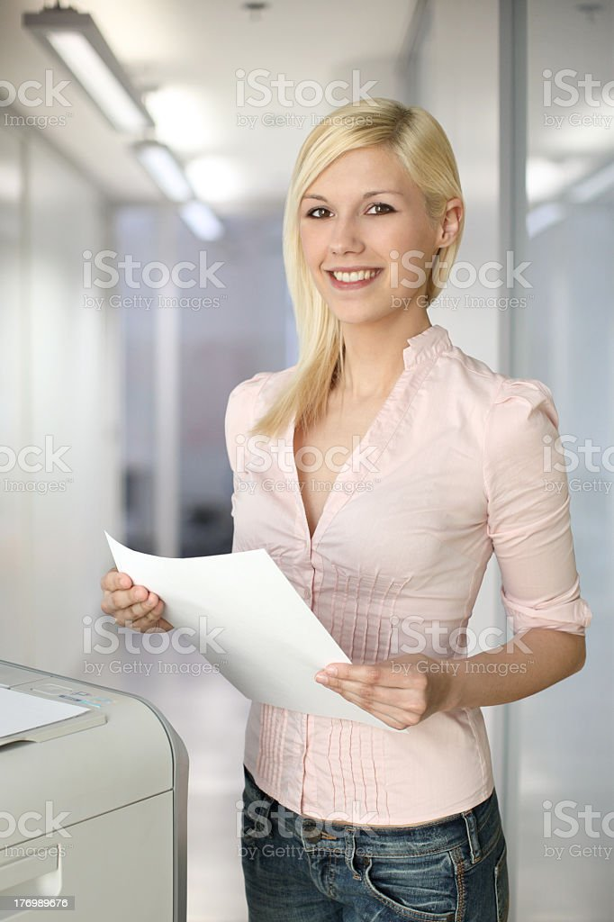Young businesswoman standing next to a photocopier stock photo
