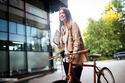 Young businesswoman standing in a city with bicycle and tablet