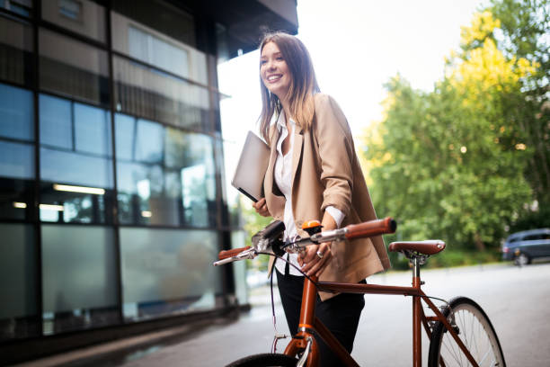 Young businesswoman standing on a city street with bicycle stock photo