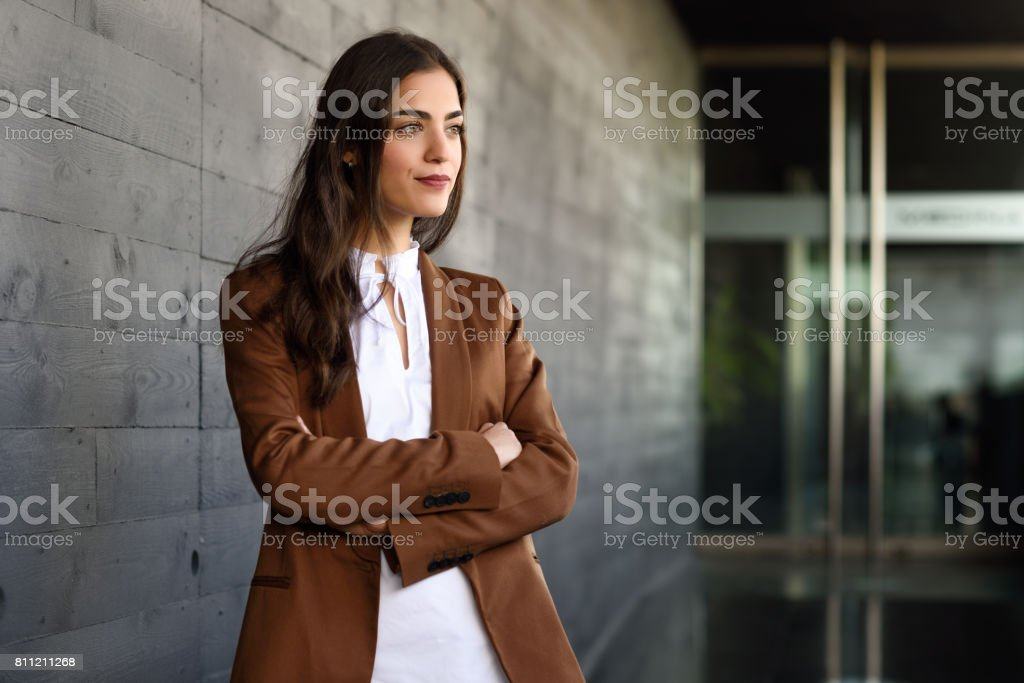 Young businesswoman standing outside of office building. stock photo