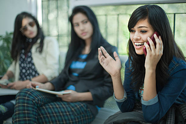 Young businesswoman talking loud on phone in office waiting room. Indoor image of a young businesswoman sitting and talking loudly on phone without care which is causing disturbance for others in a waiting room of an office. Three people, waist up, horizontal composition with selective focus. inconvenience stock pictures, royalty-free photos & images