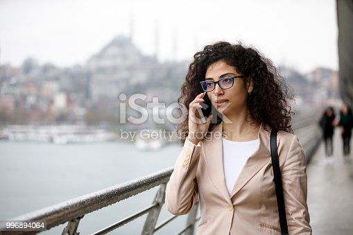 Young businesswoman talking on the phone in the street in Istanbul, Turkey