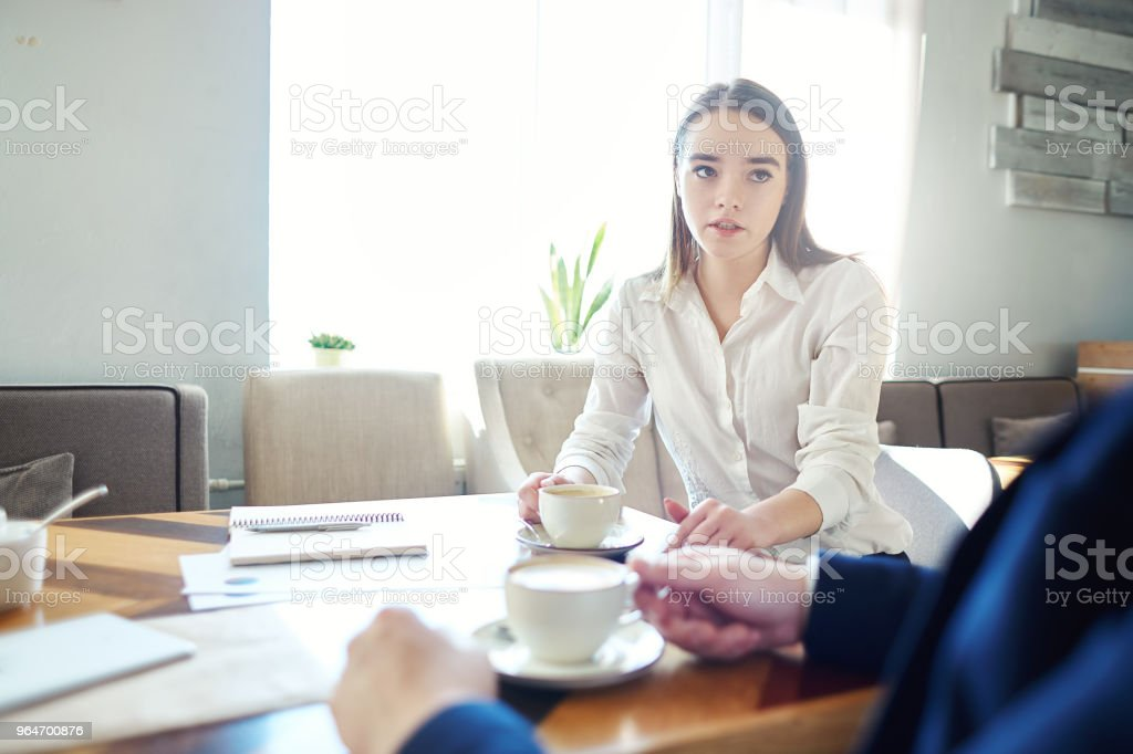 Young businesswoman talking to unrecognizable male colleague during coffee meting in cafe, documents and notebooks on table royalty-free stock photo