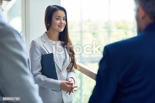 istock Young Businesswoman Talking with Colleagues 886650790