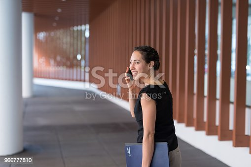 A young ethnic businesswoman carries her notes and folders as she talks on the phone and walks to a conference. She is on a sidewalk outside a conference center.