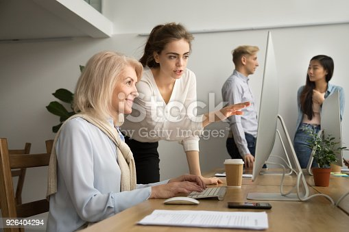 926404274 istock photo Young businesswoman teaching smiling senior colleague explaining computer applications work 926404294
