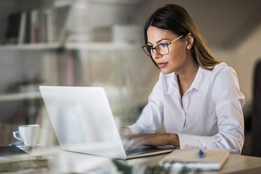 istock Young businesswoman typing an e-mail on laptop at home office. 1072035598