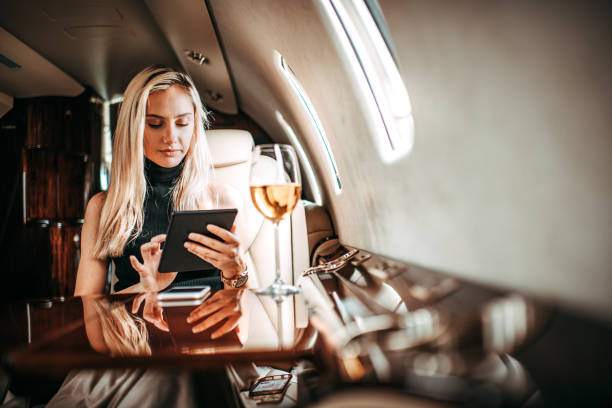 Young businesswoman using a digital tablet while traveling in a private jet Young successful businesswoman traveling aboard a private airplane. She is using a digital tablet. status symbol stock pictures, royalty-free photos & images