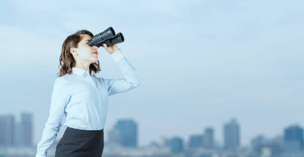Young businesswoman using binoculars in front of the city. stock photo