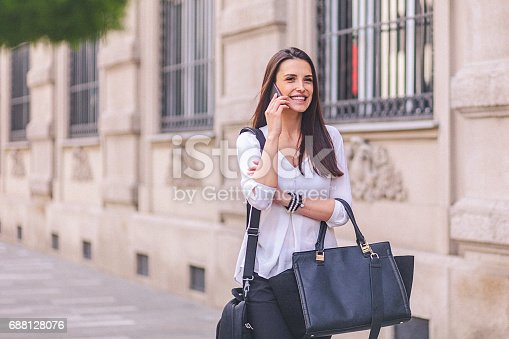 Close-up of a young businesswoman using a mobile phone while walking through the urban environment. The woman has a long dark hair and carries a big black handbag and a briefcase hang on a shoulder. The shot is executed with available natural light, and the copy space has been left. Shallow DOF. Soft focused.