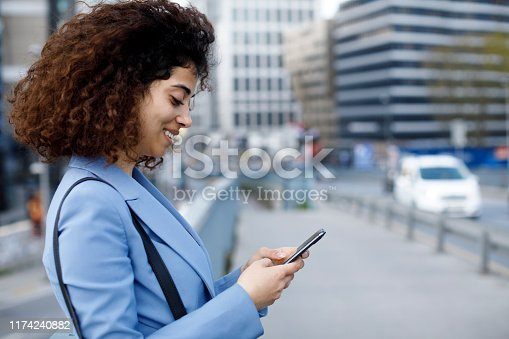 istock Young businesswoman using cellphone on city street 1174240882