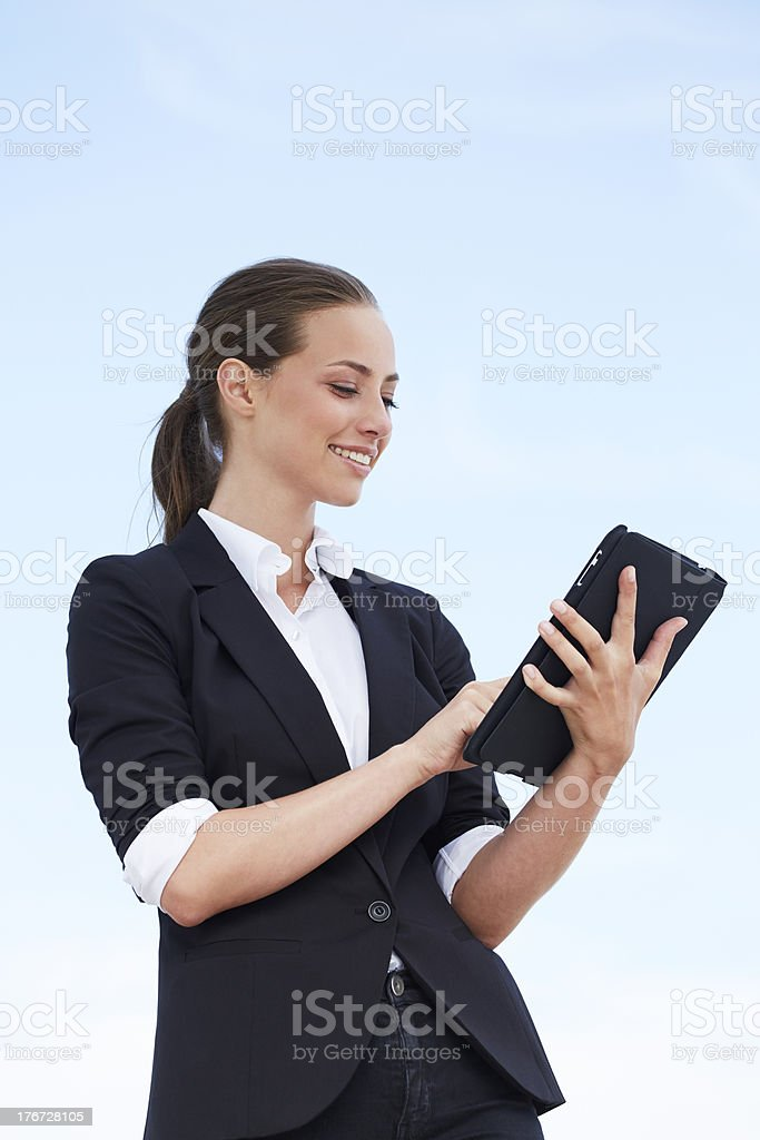 Young businesswoman using digital tablet against blue sky royalty-free stock photo