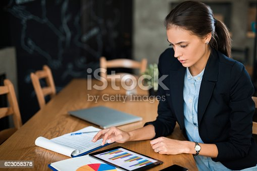 Young thoughtful businesswoman siiting at the office, using digital tablet and analyzing business report. Copy space.