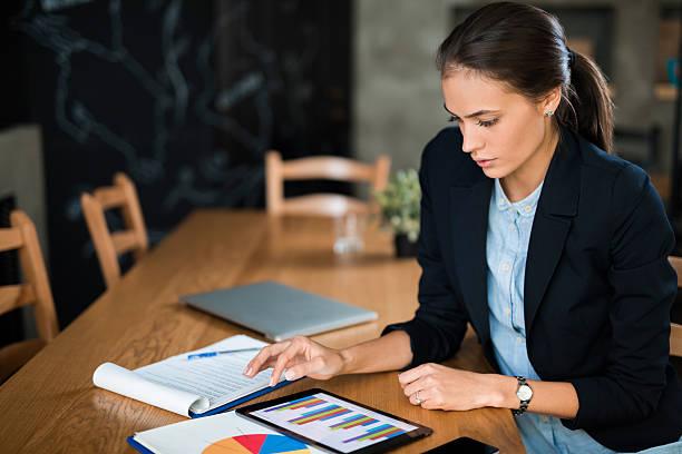young businesswoman using digital tablet and analyzing business report. - rapporto finanziario foto e immagini stock