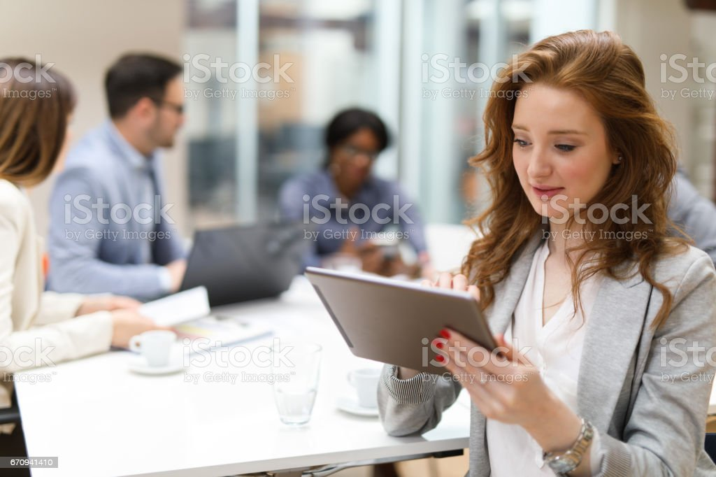 Young businesswoman using digital tablet and analyzing business report. stock photo
