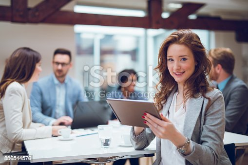 istock Young businesswoman using digital tablet and analyzing business report. 886544576