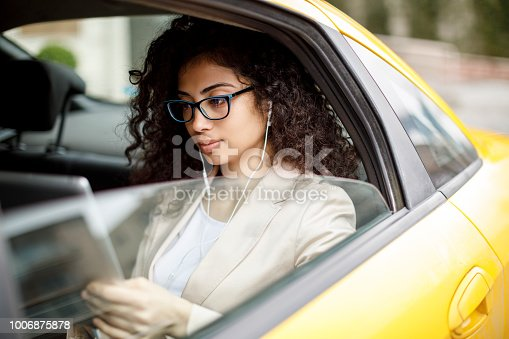 Young businesswoman using digital tablet in a taxi