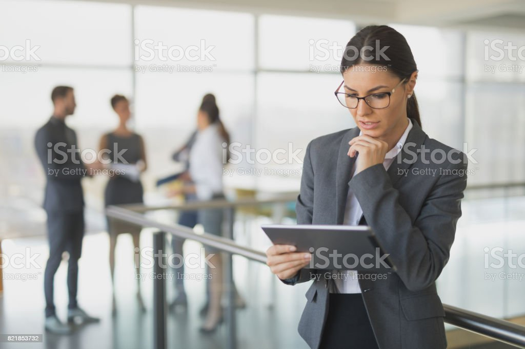 Young businesswoman using digital tablet in office building hallway stock photo