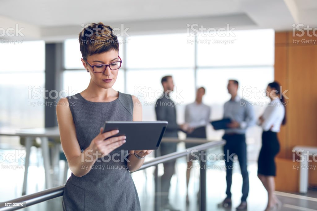 Young businesswoman using digital tablet in office building hallway. stock photo