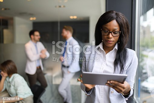 Portrait of young businesswoman in the office analyzing business report using digital tablet.There are coworkers in the background cooperating.