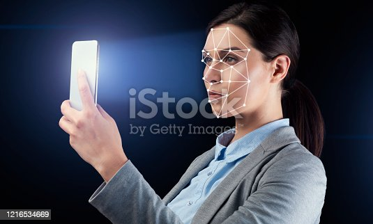 1021681352 istock photo Young businesswoman using facial recognition system for data protection on black background 1216534669
