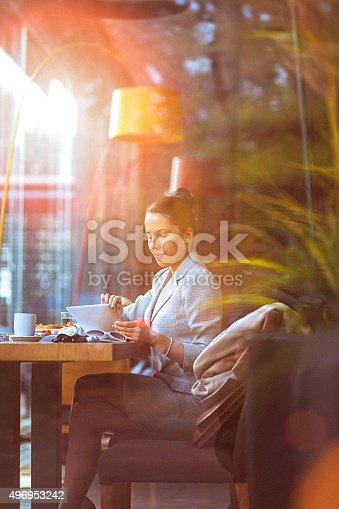 Young, trendy businesswoman using her digital tablet at a restaurant. Long dark hair tied in a bun, formalwear.