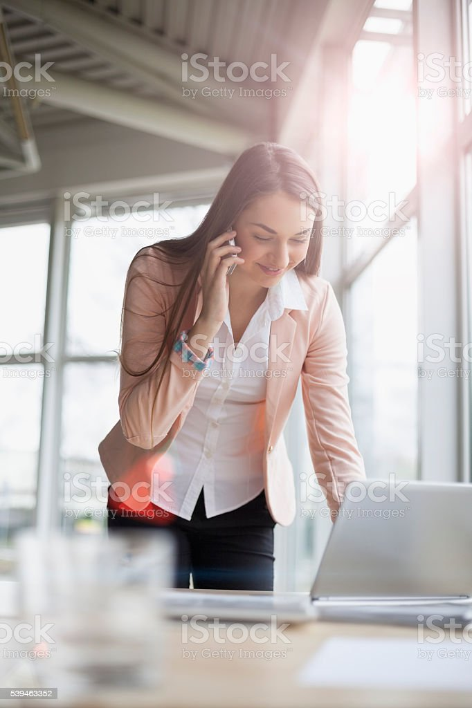 Junge Geschäftsfrau benutzt Laptop und Handy im Büro – Foto