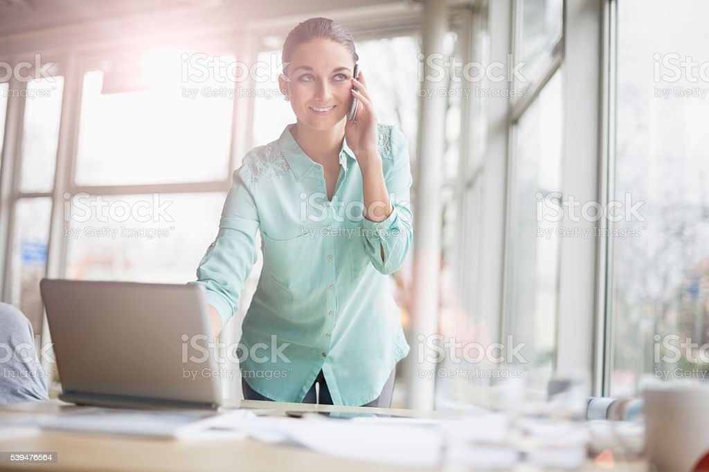 Young businesswoman using laptop and cell phone in office stock photo