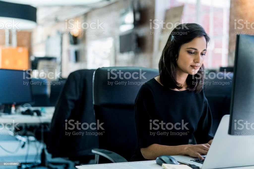 Young businesswoman using laptop at desk in office Young businesswoman using laptop at desk. Female professional is working in office. She is in businesswear. 25-29 Years Stock Photo