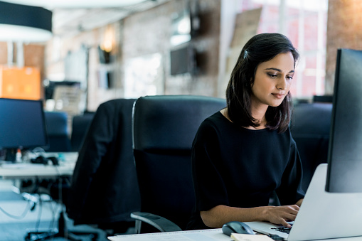 Young Businesswoman Using Laptop At Desk In Office Stock Photo - Download Image Now