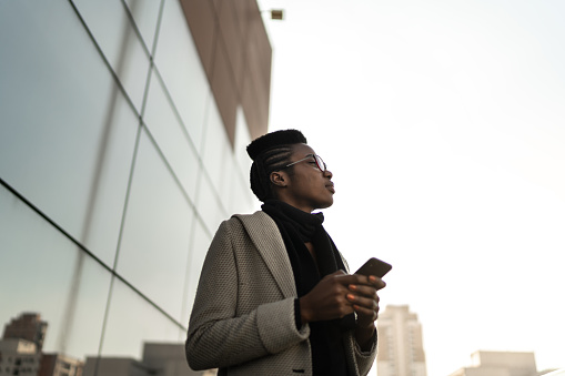Young businesswoman using mobile phone and looking away at office rooftop