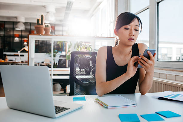 Young businesswoman using mobile phone at work stock photo