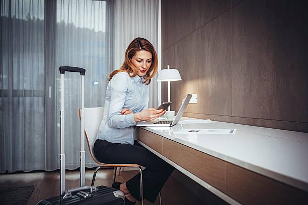 Junge Geschäftsfrau mit Mobiltelefon im Hotel Zimmer – Foto